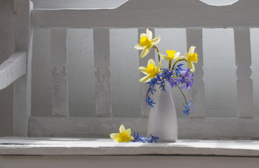 spring flowers in vase on white wooden bench