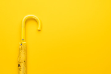 folded umbrella on the yellow background with copy space