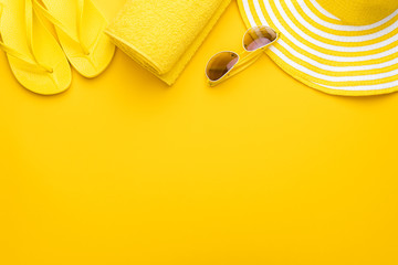 beach accessories on the yellow background - sunglasses, towel. flip-flops and striped hat. summer...