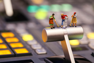 Miniature people : Maid or Housewife cleaning on Switcher buttons in studio TV station, Audio and Video Production Switcher of Television Broadcast.