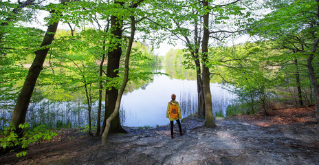 a woman is standing on a lonely forest lake in spring