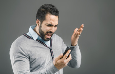 Bearded handsome man with angry face expression holding smartphone in hand on grey isolated background