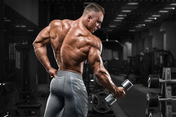 Rear view muscular man showing back in gym. Strong male bodybuilder, working out Wall mural