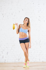 Happy young fitness woman with bananas