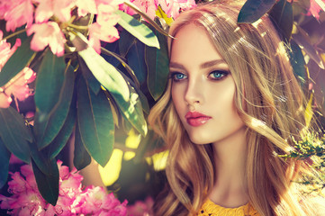 Beautiful spring model girl in flowers in summer blossom park. Woman in a blooming garden . Fashion, Cosmetics & Perfumes . Curly blonde hair