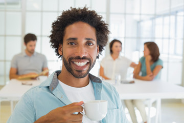 Smiling businessman having coffee with colleagues in background