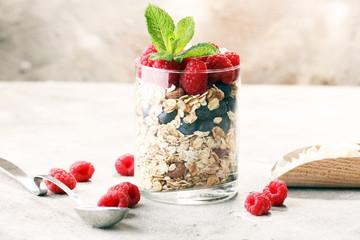 healthy breakfast with natural yogurt, muesli and berries on grey background