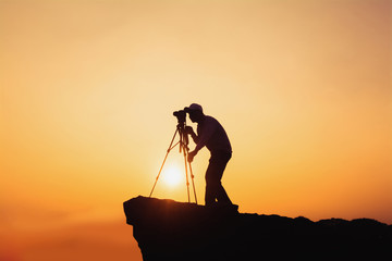 Travel concept with of photographers standing on mountain's top with camera and tripod and taking photo shots.