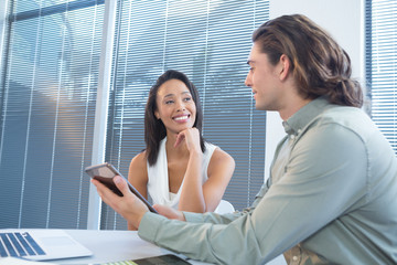 Business executives discussing over digital tablet at desk