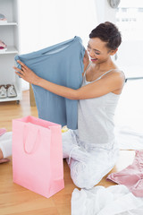 Woman on floor with new blue tshirt and shopping bag