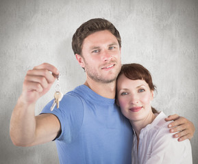Couple holding keys to home against weathered surface