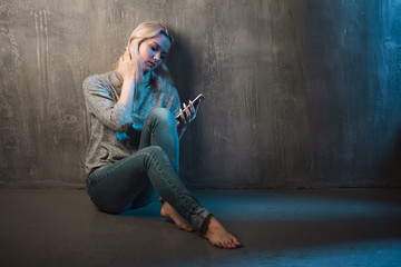 Sad young woman sitting on the floor with a phone in hands. Call waiting, no connection.