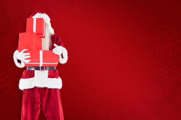 Santa covers his face with presents against red background