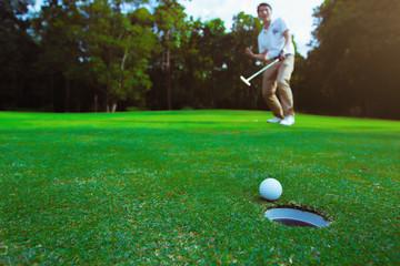 Golfer putting golf ball on the green golf.