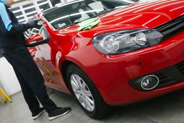Car detailing - Man with orbital polisher in repair shop polishing car. Selective focus.