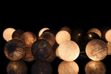 Brown and black glowing balls on a black background. Glowing garland at night. Colorful circles on the background.