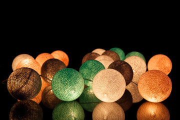 Colorful glowing balls on a black background. Glowing garland at night. Colorful circles on the background.