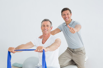 Therapist massaging a mans shoulder while gesturing thumbs up