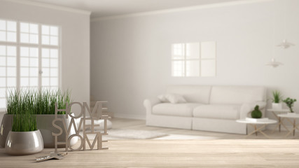 Wooden table, desk or shelf with potted grass plant, house keys and 3D letters making the words home sweet home, over scandinavian living room, architecture interior design, copy space background