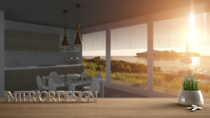 Wooden table, desk or shelf with potted grass plant, house keys and 3D letters making the words interior design, over blurred kitchen with panoramic window, project concept copy space background