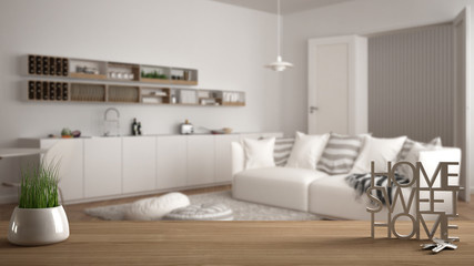 Wooden table, desk or shelf with potted grass plant, house keys and 3D letters making the words home sweet home, over modern white living room, architecture interior design, copy space background