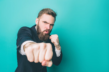 Another picture of strong guy in suite. He is showing his right fist to the camera. Thia man looks serious and brutal. Isolated on blue background.