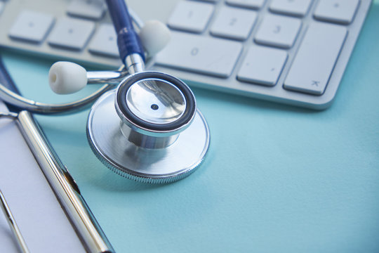Stethoscope with clipboard and Laptop on desk,Doctor working in hospital writing a prescription. Healthcare and medical concept, test results in background, selective focus