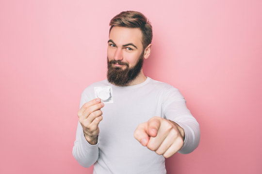 Happy man is holding a condom and pointing on camera. He is smiling. Isolated on pink background.