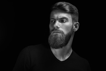 Portrait of handsome single bearded young man with serious expression looking over black background with copy space