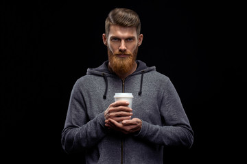 Dramatic light studio shot of young caucasian bearded stylish man with cup of coffee Handsome hairstyling male portrait holding coffee to go cup over black background .