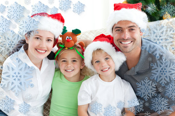 Happy family with christmas hats sitting on the sofa against snowflake frame