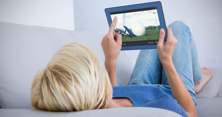 Blonde woman using her tablet on the couch against football player about to kick ball