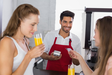 Women paying bill while drinking orange juice at coffee shop