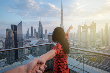 Aluminium Prints Dubai Woman is leading her partner and is pointing with her finger to the skyline of Dubai Downtown