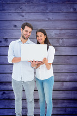Attractive young couple holding their laptop against wooden planks background