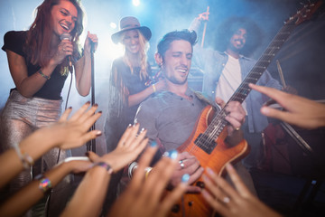 Guitarist performing by crowd at nightclub