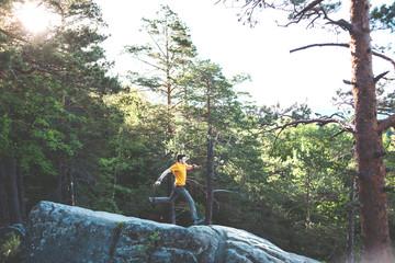 A man balances on a stone.