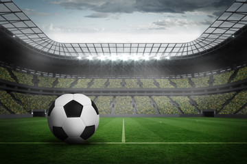 Black and white leather football in a large football stadium with fans in yellow