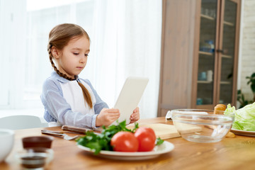 Adorable little girl wearing apron browsing Internet on digital tablet in order to find recipe of appetizing starter while wrapped up in making surprise for birthday of her dad