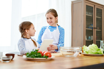 Cheerful little sisters wearing aprons looking at each other with wide smiles while preparing appetizing starter for their parents, spacious kitchen interior on background