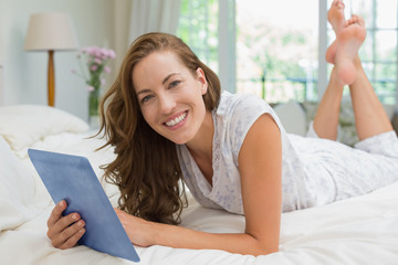 Happy young woman using digital tablet in bed