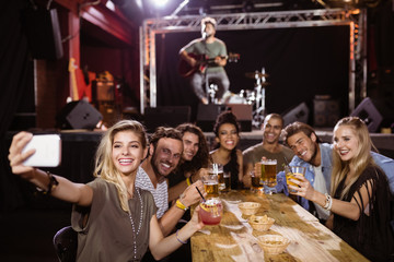 cheerful friends taking selfie while sitting at table with performer singing on stage