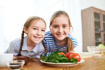 Adorable little sisters looking at camera with wide smiles while standing at wooden table and preparing healthy snack for their parents, group portrait shot