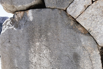 White mable carved with ancient inscription of greek text on the rock of monument, Temple of Apollo, Delphi, Greece. The inscription is difficult to distinguish