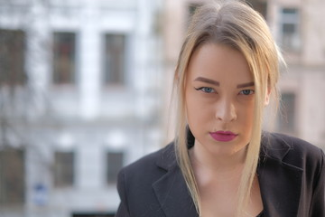 Portrait of a young woman in a black suit close-up against a background of a blurry city in the rays of the setting sun.