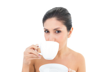 Pretty brunette holding a cup and saucer and taking a sip