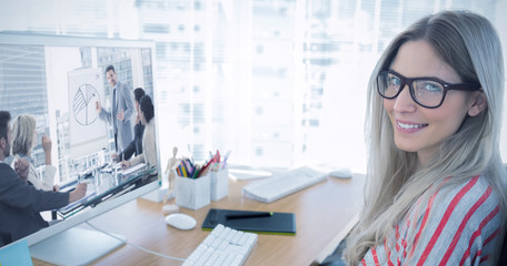 Attractive photo editor working on computer against business people in office at presentation