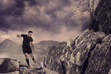 Rugby player kicking the ball against rock crashing down from cliff