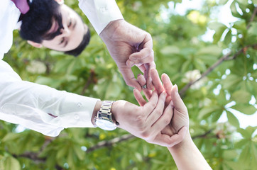 Picture of man putting engagement silver ring on woman hand, outdoor, ant or below view