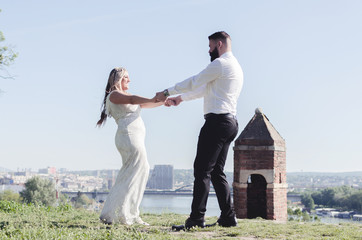 Just married couple dancing valse outdoor, free space.